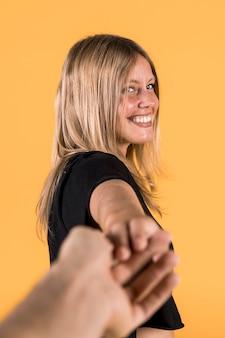 黄色の壁に対して彼女のボーイフレンドを引っ張って笑顔の若い女性