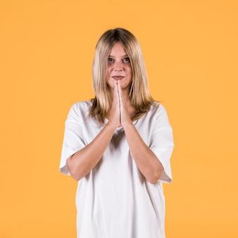 黄色の壁に立っているジェスチャーの祈りと笑顔の若い女性の肖像画