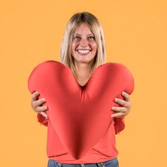 赤いハート形のクッションを誰かに与える笑顔の聴覚障害者の女性