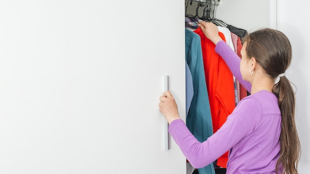 女の子は学校のための服を選ぶ