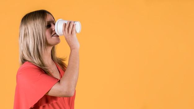 黄色の背景上の使い捨てのガラスにジュースを飲む若い女性の笑みを浮かべてください。