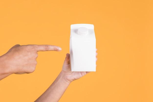 黄色の背景上の白いテトラパックを指している人の手