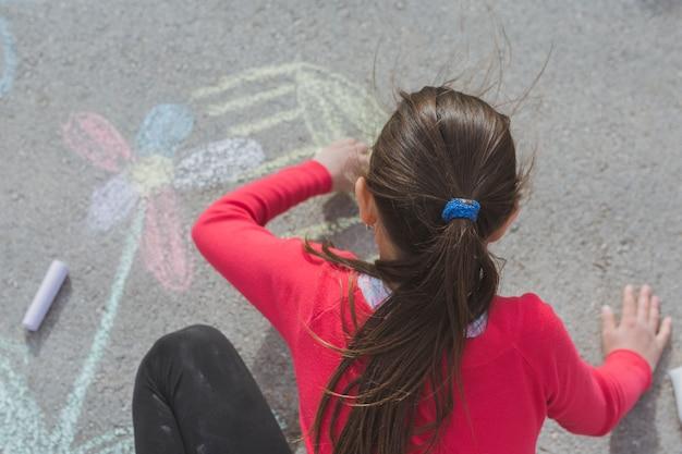 チョークで道路上を描く少女