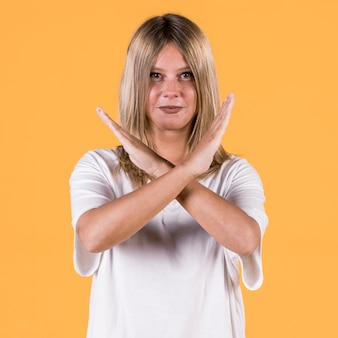 笑顔を無効に黄色の背景に対して手話で警告ジェスチャーを示す女性