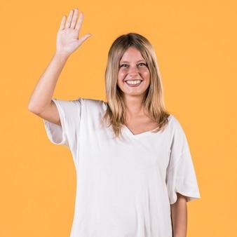 腕を持つ幸せな聴覚障害者の女性は、普通の背景の前に立って発生