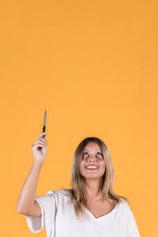 黄色の背景に見上げるペンを保持している若い女性の笑みを浮かべてください。