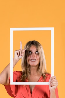 Улыбающаяся женщина-инвалид с рамой, направленная вверх на ровную поверхность