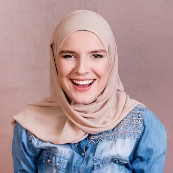 色付きの背景の前で笑っているスカーフとイスラム教徒の女性
