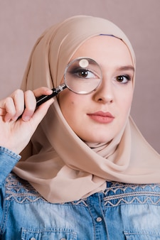 Крупный план мусульманской женщины, глядя через увеличительное стекло
