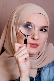 Крупный план любопытно мусульманская женщина, глядя через увеличительное стекло