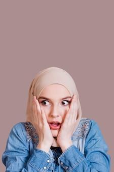 スタジオの背景の上の覆われた頭を持つかなりショックを受けたイスラム教徒の女性