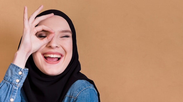 Молодая исламская радостная женщина, держащая пальцы в хорошо жесте по ее глазу