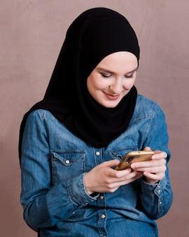 Привлекательная женщина улыбается с помощью мобильного телефона на фоне