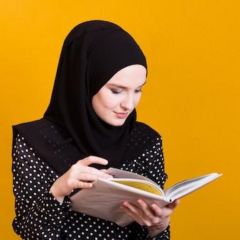 明るい黄色の背景上の教科書を読んでかなりアラブ女性