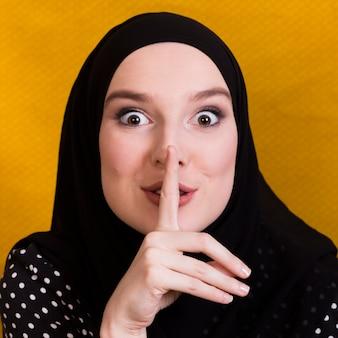 背景に沈黙のジェスチャーを作るアラビアの女性のクローズアップ