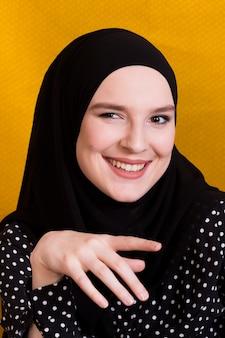 黄色の背景に対してカメラを見て陽気なイスラムの女性の肖像画