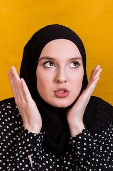 黄色の背景にヒジャーブを着ている怒っているイスラム教徒の女性