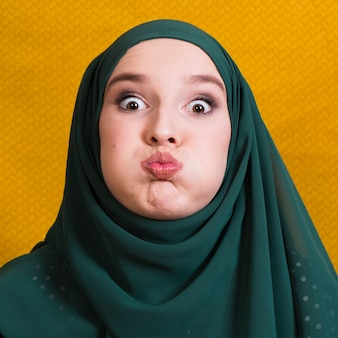 黄色の背景の前に面白い表情を作るイスラム教徒の女性の肖像画