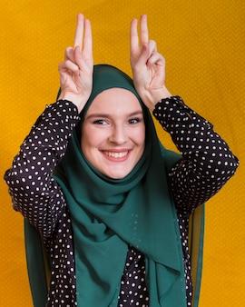 黄色の背景の前に変な顔をするイスラムの女性の笑みを浮かべてください。