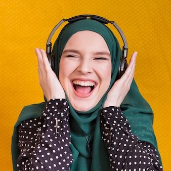 陽気な若いアラビア女性が黄色の背景に対してヘッドフォンで音楽を聴く