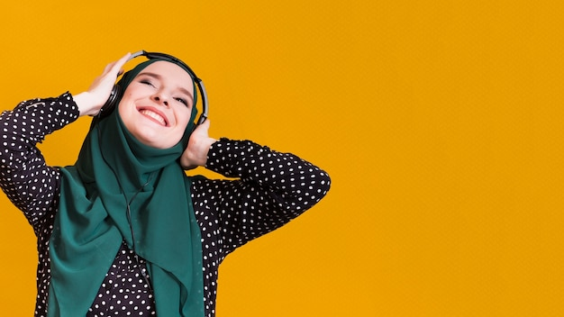 幸せなイスラム教徒の女性が黄色の表面に対してヘッドフォンで曲を聴く