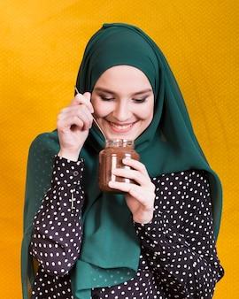 チョコレートの瓶とスプーンを黄色の背景に対して保持している笑顔の女性の正面図