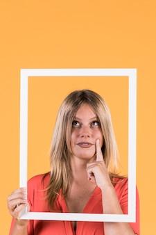 黄色の背景にフレームの切り欠きを保持している思いやりのある聴覚障害者の女性