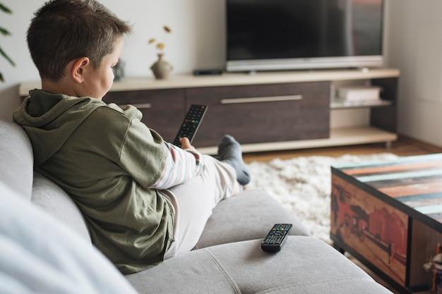 家でテレビを見ている少年