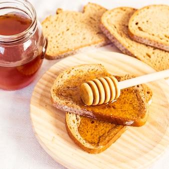 Крупным планом кусочек свежей булочки с медом в деревянной тарелке