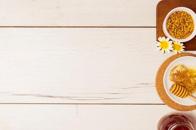 Мед; пчелиная пыльца и соты расположены в ряд над деревянным столом