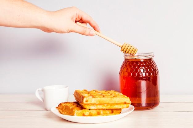 朝食に瓶から蜂蜜を選ぶひしゃくを持つ人の手
