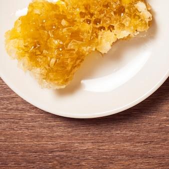 木製のテーブルの上の皿に有機天然ハニカムのクローズアップ