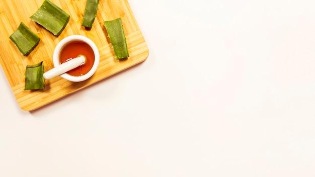 白い背景に分離された木製のまな板の上の蜂蜜とアロエベラのスライス