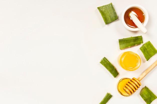 Повышенный вид ломтика алоэвера и меда для приготовления лекарств