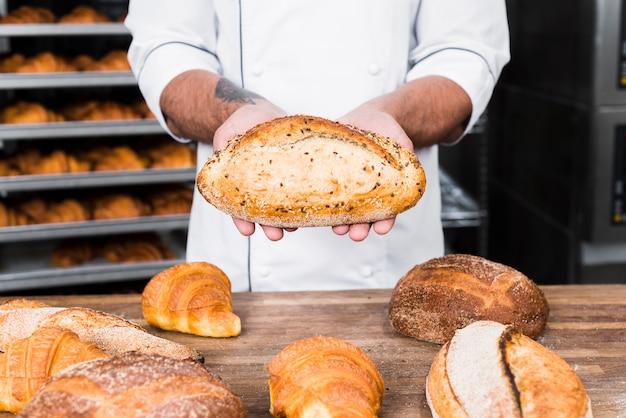 焼きたてのパンを保持している男性のパン屋のクローズアップ
