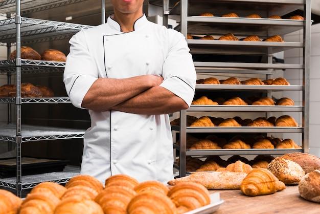 彼の腕を持つ男性のパン屋の中央部はパン屋で立っている交差