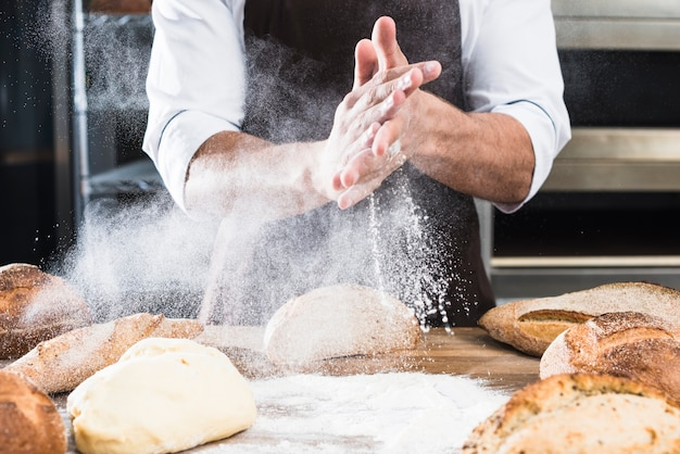焼きたてのパンと木の机の上に小麦粉を散布男性のパン屋さんの手のクローズアップ