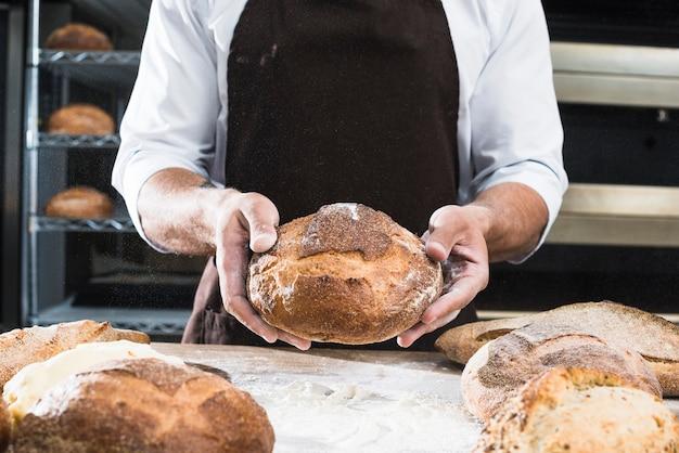 Крупным планом мужской пекарь, показывая буханку хлеба