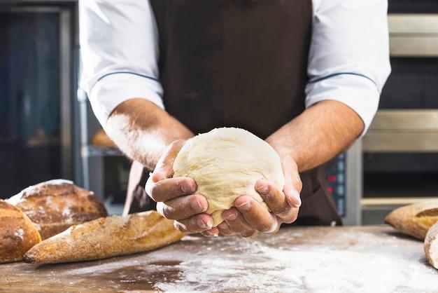 挽きたての生地を持っている男性のパン屋さんの手のクローズアップ