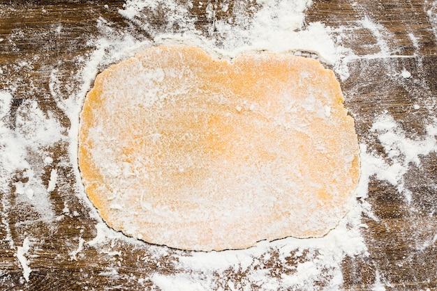 Плоское тесто с белой мукой на деревянной поверхности