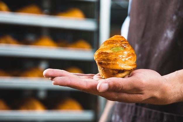 焼きたての甘いパフペーストリーを持っている男性のパン屋さんの手のクローズアップ