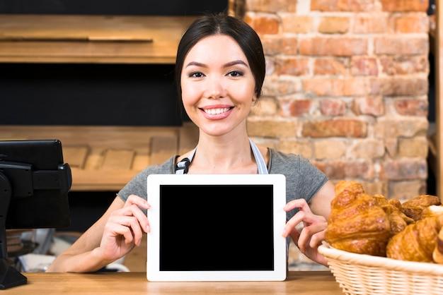 Портрет улыбающейся молодой женщины, показывающей цифровую таблетку около круассана на прилавке пекарни