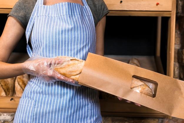 Женщина-пекарь в фартуке упаковывает хлеб в багет в коричневый бумажный пакет