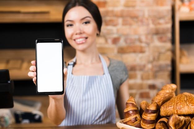 Расфокусированные женщина-пекарь стоит за прилавком, показывая мобильный телефон