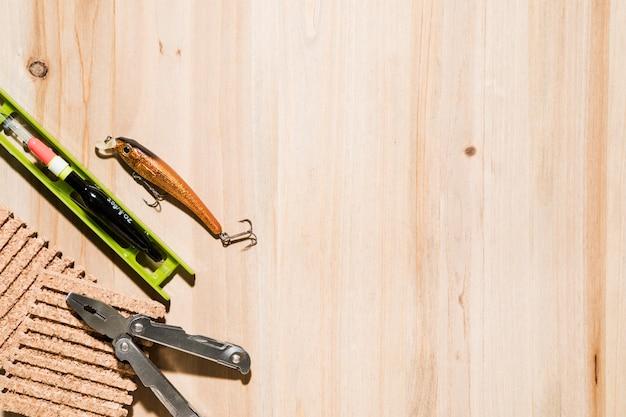 釣りのルアー。フロート釣りコルクボードと机の上のペンチ