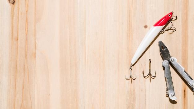 Поднятый вид красной и белой рыболовной приманки с крючком и плоскогубцами на деревянном фоне поверхности