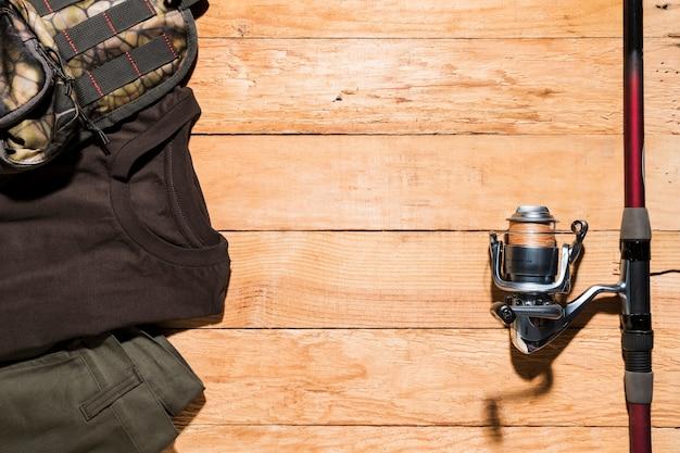 男性のアクセサリーと木製の机の上の釣り竿