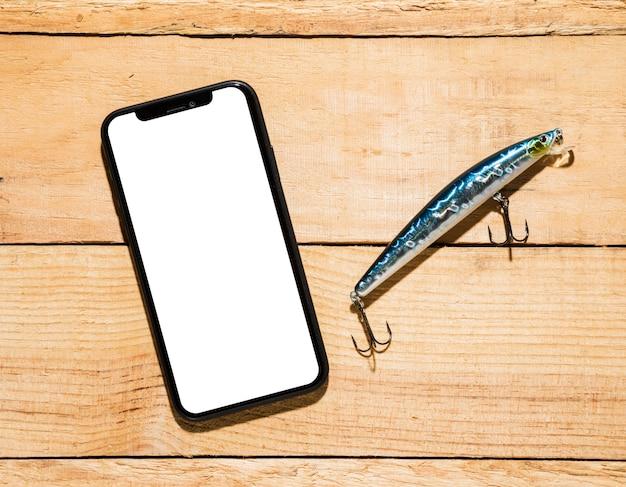 白い画面表示と木製の机の上のフック付き釣りルアー付き携帯電話