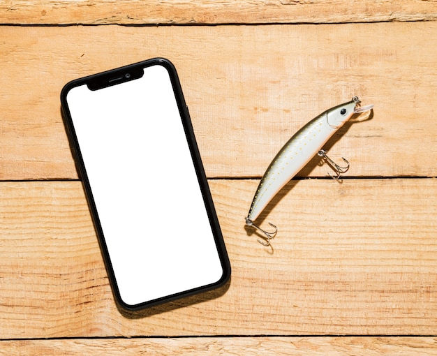 白い画面表示と木製の机の上の釣りのルアー付き携帯電話