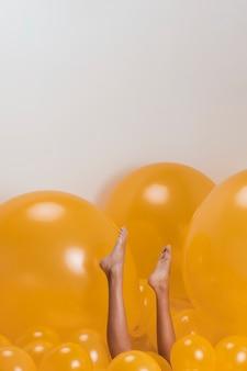 多くの黄色い風船の間の女性の足